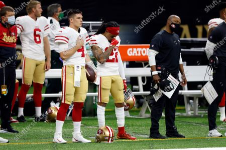 San Francisco 49ers quarterback Nick Mullens (4) and cornerback Jason Verrett (22) during the National Anthem before an NFL football game against the New Orleans Saints, in New Orleans