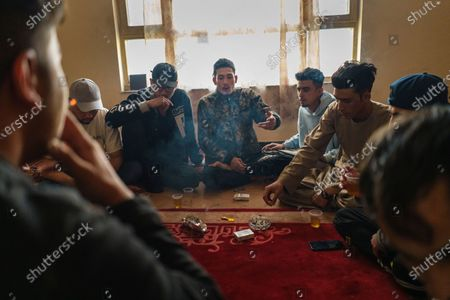 Jawad Sezdah, center, and his fellow rappers at their music studio OLBR recordO in the Pul-e-Surkhta neighborhood of Kabul, Afghanistan, on Saturday Oct. 24, 2020. Jawad Sezdah and his friends are artists who raps AfghanistanOs darkening future. Most days they sit around a circle at their Oclub,O a second-floor makeshift studio with a picture of Tupac Shakur is taped on the wall, in west KabulOs Pul-e-Surkhta neighborhood. They smoke weed, drink tea, and practice freestyle lyrics and breakdance together. (Marcus Yam / Los Angeles Times)