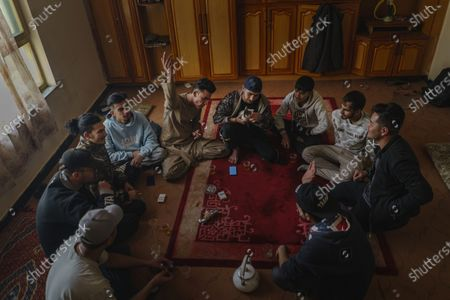 Stock Photo of Saher Melody, clockwise from left, Sajad Temurian, Jawad Sezdah, Hadi Hashemi, Soaban Fareed, SeraJ AaToon AaToor, Hasib Ahmadi, Qais Khaksar, Hamed Bass, and Tamim Mats practice their free styling lyrics at their music studio OLBR recordO in the Pul-e-Surkhta neighborhood of Kabul, Afghanistan, on Saturday Oct. 24, 2020. Jawad Sezdah and his friends are artists who raps AfghanistanOs darkening future. Most days they sit around a circle at their Oclub,O a second-floor makeshift studio with a picture of Tupac Shakur is taped on the wall, in west KabulOs Pul-e-Surkhta neighborhood. They smoke weed, drink tea, and practice freestyle lyrics and breakdance together. (Marcus Yam / Los Angeles Times)