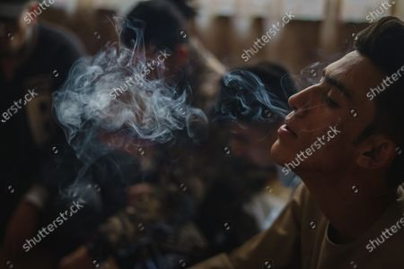 Soaban Fareed, center, exhales smoke as he sits with his fellow rappers at their music studio OLBR recordO in the Pul-e-Surkhta neighborhood of Kabul, Afghanistan, on Saturday Oct. 24, 2020. Jawad Sezdah and his friends are artists who raps AfghanistanOs darkening future. Most days they sit around a circle at their Oclub,O a second-floor makeshift studio with a picture of Tupac Shakur is taped on the wall, in west KabulOs Pul-e-Surkhta neighborhood. They smoke weed, drink tea, and practice freestyle lyrics and breakdance together. (Marcus Yam / Los Angeles Times)