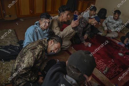 Stock Picture of Jawad Sezdah, bottom left, reacts to a joke made by hisfellow rappers at their music studio OLBR recordO in the Pul-e-Surkhta neighborhood of Kabul, Afghanistan, on Saturday Oct. 24, 2020. Jawad Sezdah and his friends are artists who raps AfghanistanOs darkening future. Most days they sit around a circle at their Oclub,O a second-floor makeshift studio with a picture of Tupac Shakur is taped on the wall, in west KabulOs Pul-e-Surkhta neighborhood. They smoke weed, drink tea, and practice freestyle lyrics and breakdance together. (Marcus Yam / Los Angeles Times)