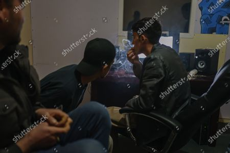 Stock Image of Soaban fareed, right, takes a whiff of a cigarette before recording new music with their fellow rappers at their music studio OLBR RecordsO in the Pul-e-Surkhta neighborhood of Kabul, Afghanistan, on Friday Oct. 30, 2020. Jawad Sezdah and his friends are artists who raps AfghanistanOs darkening future. Most days they sit around a circle at their Oclub,O a second-floor makeshift studio with a picture of Tupac Shakur is taped on the wall, in west KabulOs Pul-e-Surkhta neighborhood. They smoke weed, drink tea, and practice freestyle lyrics, record music and breakdance together. (Marcus Yam / Los Angeles Times)