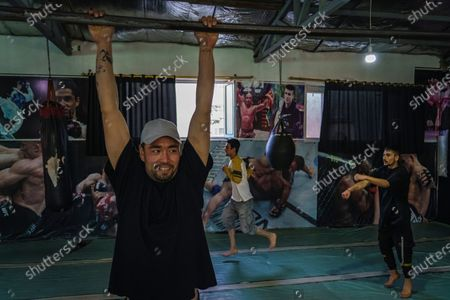 """Saher Melody tries to do a pull up as he and his friends warm up before they practice breakdancing at a local gym in the in the Pul-e-Surkhta neighborhood of Kabul, Afghanistan, on Thursday Oct. 22, 2020. Jawad Sezdah and his friends are artists who raps Afghanistan's darkening future. Most days they sit around a circle at their """"club,"""" a second-floor makeshift studio with a picture of Tupac Shakur is taped on the wall, in west Kabul's Pul-e-Surkhta neighborhood. They smoke weed, drink tea, and practice freestyle lyrics and breakdance together. (Marcus Yam / Los Angeles Times)"""