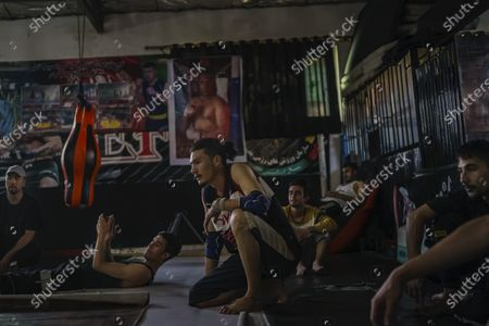 Jawad Sezdah, center, practice his breakdancing skills at a local boxing gym in the Pul-e-Surkhta neighborhood of Kabul, Afghanistan, on Thursday Oct. 22, 2020. Jawad Sezdah and his friends are artists who raps AfghanistanOs darkening future. Most days they sit around a circle at their Oclub,O a second-floor makeshift studio with a picture of Tupac Shakur is taped on the wall, in west KabulOs Pul-e-Surkhta neighborhood. They smoke weed, drink tea, and practice freestyle lyrics and breakdance together. (Marcus Yam / Los Angeles Times)