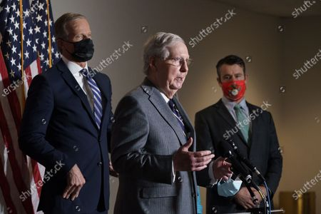 Senate Majority Leader Mitch McConnell, R-Ky., flanked by Sen. John Thune, R-S.D., left, and Sen. Todd Young, R-Ind., talks to reporters after a Republican Conference luncheon, on Capitol Hill in Washington