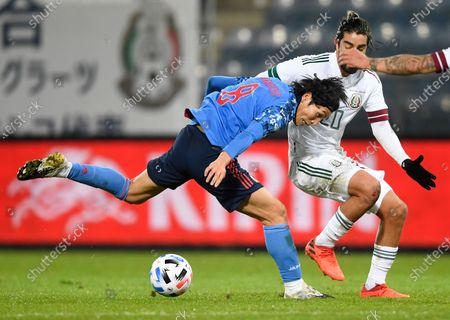 Genki Haraguchi, left, and Mexico's Rodolfo Pizarro compete for the ball during the international friendly soccer match between Japan and Mexico at the Liebenauer Stadium in Graz, Austria
