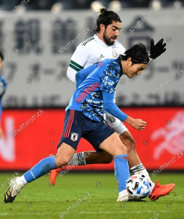 Genki Haraguchi, front, and Mexico's Rodolfo Pizarro compete for the ball during the international friendly soccer match between Japan and Mexico at the Liebenauer Stadium in Graz, Austria