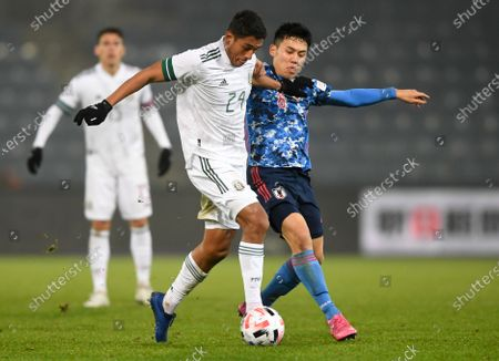 Mexico's Luis Romo, left, and Japan's Wataru Endo battle for the ball during the international friendly soccer match between Japan and Mexico at the Liebenauer Stadium in Graz, Austria