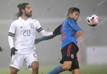 Japan's Wataru Endo, right, and Mexico's Rodolfo Pizarro compete for the ball during the international friendly soccer match between Japan and Mexico at the Liebenauer Stadium in Graz, Austria