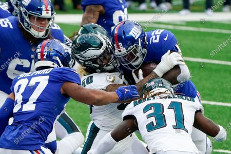 New York Giants running back Wayne Gallman (22) is stopped near the end zone by Philadelphia Eagles middle linebacker Duke Riley (50) and cornerback Nickell Robey-Coleman (31) in the second half of an NFL football game, in East Rutherford, N.J