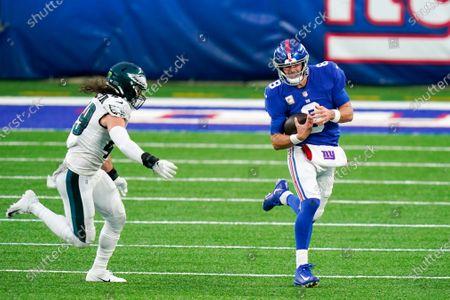 New York Giants quarterback Daniel Jones (8) is pursued by Philadelphia Eagles linebacker Alex Singleton (49) in the second half of an NFL football game, in East Rutherford, N.J