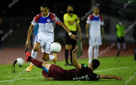 Chile's Alexis Sanchez, left, and Venezuela's Luis del Pino battle for the ball during a qualifying soccer match for the FIFA World Cup Qatar 2022 in Caracas, Venezuela