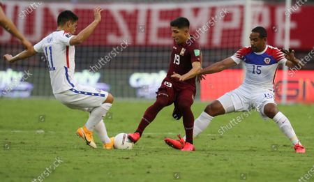 Venezuela's Jefferson Savarino, center, fight for the ball with Chile's Jean Beausejour, right, and Felipe Mora during a qualifying soccer match for the FIFA World Cup Qatar 2022 in Caracas, Venezuela