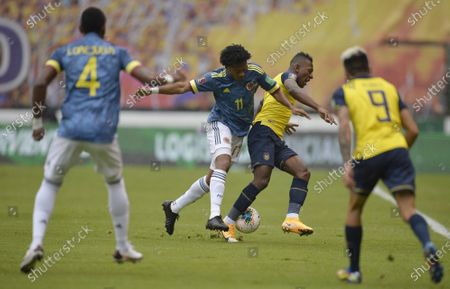 Colombia's Juan Cuadrado, second left, fights for the ball with Ecuador's Pervis Estupinan, second right, during a qualifying soccer match for the FIFA World Cup Qatar 2022 in Quito, Ecuador