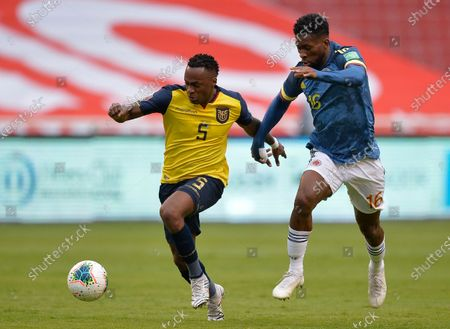Ecuador's Renato Ibarra, left, battles for the ball with Colombia's Jefferson Lerma during a qualifying soccer match for the FIFA World Cup Qatar 2022 in Quito, Ecuador