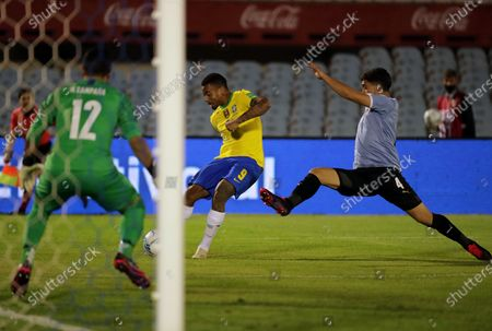Gabriel Jesus (C) of Brazil kicks the ball defended by the Uruguayan goalkeeper Martin Campana (L) and under pressure of the player Agustin Oliveros (R) of Uruguay during a match of the South American Qualifiers for the World Cup in Qatar between the teams of Uruguay and Brazil, at the Centenario stadium in Montevideo, Uruguay, 17 November 2020.
