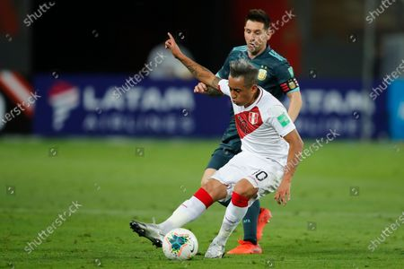 Peru's Christian Cueva, front, and Argentina's Lionel Messi battle for the ball during a qualifying soccer match for the FIFA World Cup Qatar 2022 in Lima, Peru