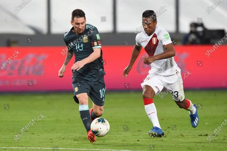 Argentina's Lionel Messi, left, and Peru's Pedro Aquino battle for the ball during a qualifying soccer match for the FIFA World Cup Qatar 2022 in Lima, Peru
