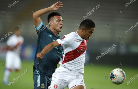 Argentina's Lautaro Martinez, left, and Peru's Anderson Santamaria battle for the ball during a qualifying soccer match for the FIFA World Cup Qatar 2022 in Lima, Peru