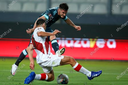 Peru's Aldo Corzo, front, and Argentina's Nicolas Tagliafico battle for the ball during a qualifying soccer match for the FIFA World Cup Qatar 2022 in Lima, Peru