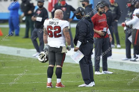 Tampa Bay Buccaneers center A.Q. Shipley (62) chats with assistant head coach Harold Goodwin during an NFL football game against the Carolina Panthers, in Charlotte, N.C