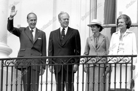 President Valéry Giscard d'Estaing of France, left, waves to the crowd to the crowd as United States President Gerald R. Ford, left center, looks on as he is welcomed to the White House in Washington, DC for a State Visit. Anne-Aymone Giscard d'Estaing, right center, and first lady Betty Ford, right, are pictured with their husbands.
