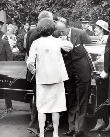 President Valéry Giscard d'Estaing of France, right center, kisses the hand of Mrs. Betty Ford as he emerges from his limo prior to the arrival ceremony in his honor at the White House in Washington, DC for a State Visit. Anne-Aymone Giscard d'Estaing is in the background at right.