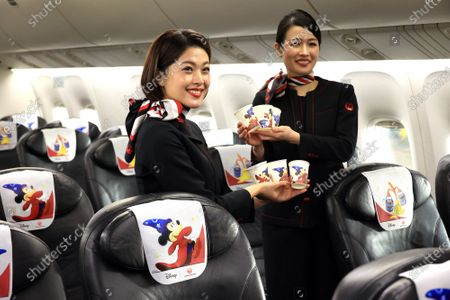 "Japan Airlines' (JAL) cabin attendants display special designed headrest covers and paper cups in a special designed airplane to celebrate the 80th anniversary of Walt Disney's animated film ""Fantasia"" which had the first screening in 1940 at a JAL hangar at Tokyo's Haneda airport on Wednesday, November 18, 2020. The special designed plane ""JAL Dream Express Fantasia 80"" is provided for a chartered pleasure flight on November 18 then served into domestic flights."