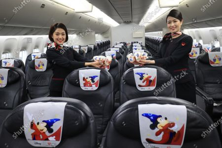 "Stock Photo of Japan Airlines' (JAL) cabin attendants display special designed headrest covers and paper cups in a special designed airplane to celebrate the 80th anniversary of Walt Disney's animated film ""Fantasia"" which had the first screening in 1940 at a JAL hangar at Tokyo's Haneda airport on Wednesday, November 18, 2020. The special designed plane ""JAL Dream Express Fantasia 80"" is provided for a chartered pleasure flight on November 18 then served into domestic flights."