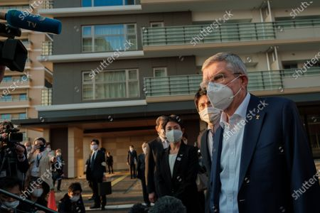 International Olympic Committee president Thomas Bach (1st R) wearing a face mask talks to journalists during a visit of Olympic and Paralympic village in Tokyo, Japan, on Nov. 17, 2020.