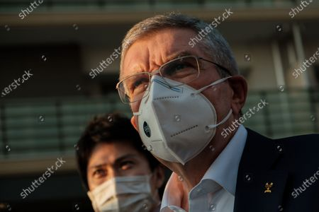 International Olympic Committee president Thomas Bach (R) wearing a face mask talks to journalists during a visit of Olympic and Paralympic village in Tokyo, Japan, on Nov. 17, 2020.