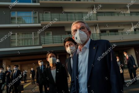 International Olympic Committee president Thomas Bach (front R) wearing a face mask talks to journalists during a visit of Olympic and Paralympic village in Tokyo, Japan, on Nov. 17, 2020.