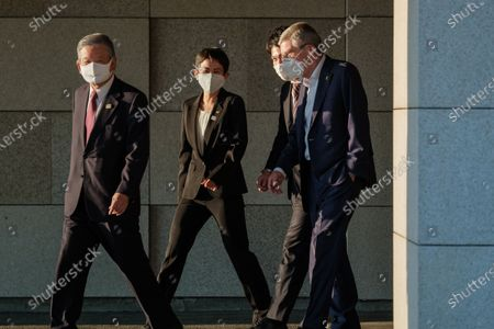 International Olympic Committee president Thomas Bach (1st R) wearing a face mask leaves an apartment facility during a visit of Olympic and Paralympic village in Tokyo, Japan, on Nov. 17, 2020.