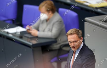 Leader of German Free Democratic Party Christian Lindner (R) speaks next to German Chancellor Angela Merkel (L) during the debate on the 3rd reform of the law for the protection of the population in the event of an epidemic situation of national scope at the German parliament Bundestag, in Berlin, Germany,18 November 2020. The infection protection law regulates measures during a pandemic such as the current spread of the Covid-19 desease.