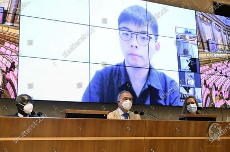 Stock Picture of (L-R) Toni Iwobi, senator of Lega party, Adolfo Urso, senator of Fratelli d'Italia and president of Farefuturo Foundation, and Laura Hart, Nonviolent Radical Party Transnational Transparty (PRNTT), attends a video-conference lesson on liberty leaded by the Hong Kong student activist and politician Joshua Wong (on screen) and organized by the Farefuturo Foundation in the Nassirya Hall of the Senate, Rome, Italy, 18 November 2020.