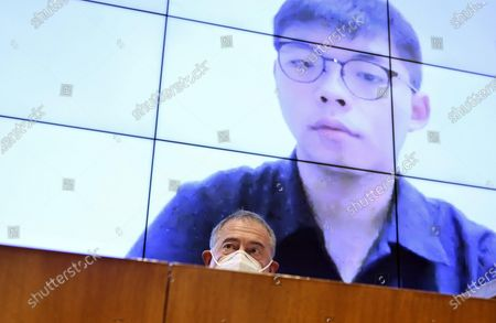 Stock Image of Adolfo Urso, senator of Fratelli d'Italia and president of Farefuturo Foundation, attends a video-conference lesson on liberty leaded by the Hong Kong student activist and politician Joshua Wong (on screen) and organized by the Farefuturo Foundation in the Nassirya Hall of the Senate, Rome, Italy, 18 November 2020.