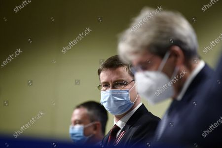 European Commission Vice-President Valdis Dombrovskis, center, looks at European Commissioner for Economy Paolo Gentiloni, right, during a joint online news conference at the EU headquarters in Brussels