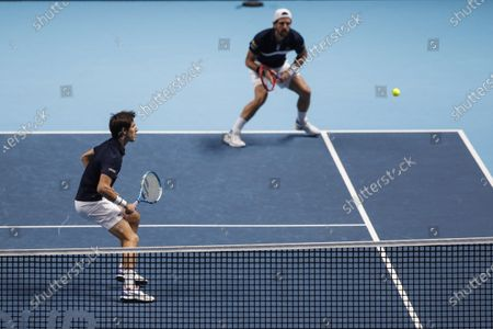 Jurgen Melzer of Austria, left, and Edouard Roger-Vasselin of France plays a return to John Peers of Australia and Michael Venus of New Zealand during their tennis match at the ATP World Finals tennis tournament at the O2 arena in London