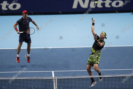 Michael Venus of New Zealand, right, and John Peers of Australia, plays a return to Jurgen Melzer of Austria during their tennis match at the ATP World Finals tennis tournament at the O2 arena in London