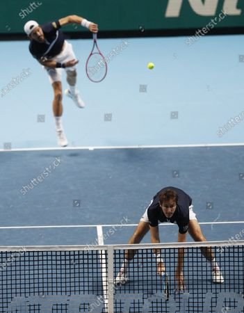 Jurgen Melzer of Austria serves and Edouard Roger-Vasselin of France watch as they play against Michael Venus of New Zealand and John Peers of Australia during their tennis match at the ATP World Finals tennis tournament at the O2 arena in London