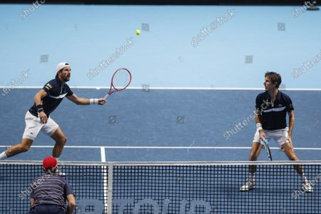 Jurgen Melzer of Austria, left, plays a return and Edouard Roger-Vasselin of France watches as they play against Michael Venus of New Zealand and John Peers of Australia during their tennis match at the ATP World Finals tennis tournament at the O2 arena in London