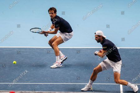 Edouard Roger-Vasselin of France, left, plays a return as Jurgen Melzer of Austria watches as they play against Michael Venus of New Zealand and John Peers of Australia during their tennis match at the ATP World Finals tennis tournament at the O2 arena in London