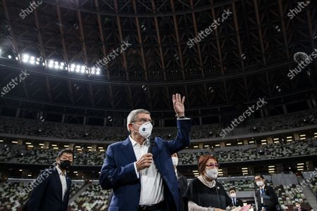 International Olympic Committee (IOC) president Thomas Bach wearing a face mask waves as he speaks to the media at the National Stadium, main venue for the 2020 Olympic and Paralympic Games postponed until July 2021 due to the COVID-19 coronavirus pandemic
