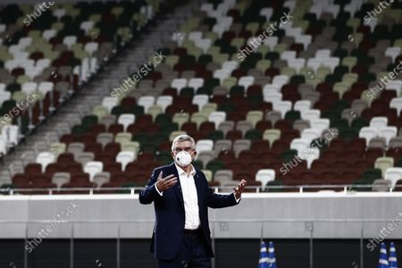 International Olympic Committee (IOC) president Thomas Bach wearing a face mask gestures as he visits the National Stadium, main venue for the 2020 Olympic and Paralympic Games postponed until July 2021 due to the COVID-19 coronavirus pandemic