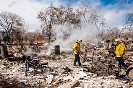 Stock Photo of Firefighters Emiliano Saldivar, center, and Chris Martinez sift through debris to recover keepsakes for residents after the Mountain View Fire tore though the Walker community in Mono County, Calif., on