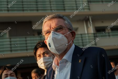International Olympic Committee President Thomas Bach (L) wearing a protective mask talks to journalists during a visit of Olympic and Paralympic village on downtown. Mr Bach is making a three-day visit to Tokyo to discuss the 2020 Olympic and Paralympic Games that were postponed because of the Covid-19 coronavirus pandemic.