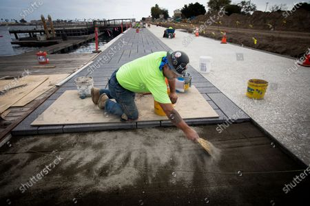 """Stock Photo of David Brown,43, Reseda is working on West Harbor on Friday, Nov. 6, 2020 in San Pedro, CA. West Harbor is located where the former Ports O' Call was located. The Ports O' Call has been mostly demolished. The new West Harbor development is in preliminary stages. The """"boardwalk"""" is being built along the water that was designed by the firm that created the High Line in Manhattan. (Francine Orr / Los Angeles Times)"""