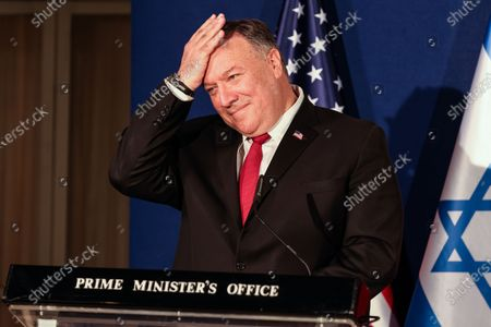 US Secretary of State Mike Pompeo pats his head during a press conference with the Israeli Prime Minister and Bahrain's Foreign Minister after their trilateral meeting