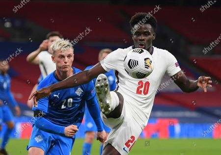England's Bukayo Saka, right, and Iceland's Albert Gudmundsson challenge for the ball during the UEFA Nations League soccer match between England and Iceland at Wembley stadium in London