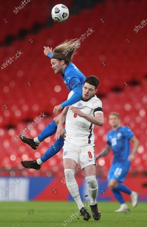 Iceland's Birkir Bjarnason, left, and England's Declan Rice challenge for the ball during the UEFA Nations League soccer match between England and Iceland at Wembley stadium in London